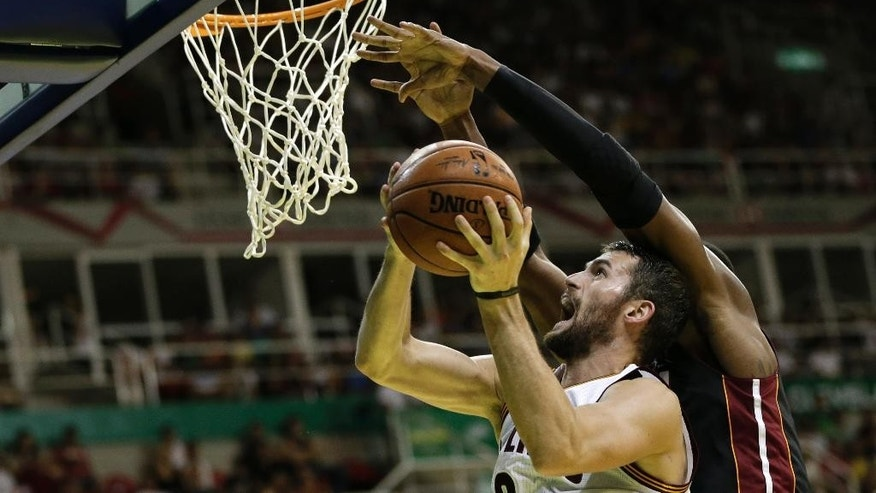 Cleveland Cavaliers' Kevin Love shoots as Miami Heat's Chris Bosh blocks him at a NBA preseason basketball game that's part of the NBA Global Games in Rio de Janeiro, Brazil, Saturday, Oct. 11, 2014. (AP Photo/Felipe Dana)