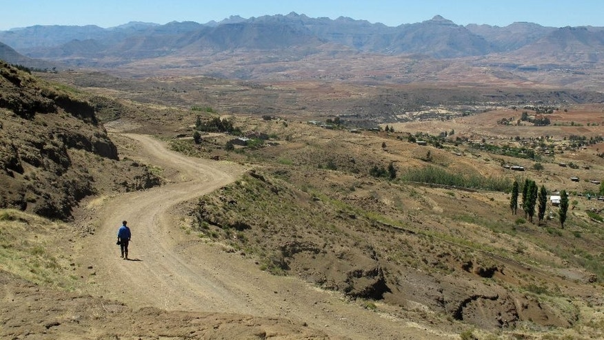 In this photo taken Sunday, Oct. 5, 2014 a man walks down a road from Gates of Paradise pass near the village of Malealea in the mountains of Lesotho on Sunday, Oct. 5, 2014. The landlocked kingdom in southern Africa is surrounded by the territory of South Africa, which has sent security forces to Lesotho to ensure order. People in Malealea are concerned that recent political unrest is keeping tourists away and will hurt development in a country struggling with poverty and AIDS. (AP Photo/Christopher Torchia)