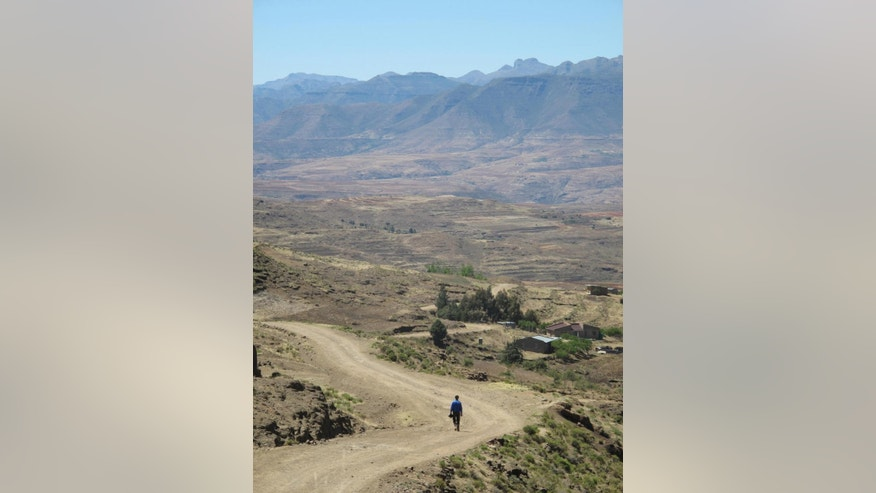 In this photo taken Sunday, Oct. 5, 2014 a man walks down a road from Gates of Paradise pass near the village of Malealea in the mountains of Lesotho. The landlocked kingdom in southern Africa is surrounded by the territory of South Africa, which has sent security forces to Lesotho to ensure order. People in Malealea are concerned that recent political unrest is keeping tourists away and will hurt development in a country struggling with poverty and AIDS. (AP Photo/Christopher Torchia)