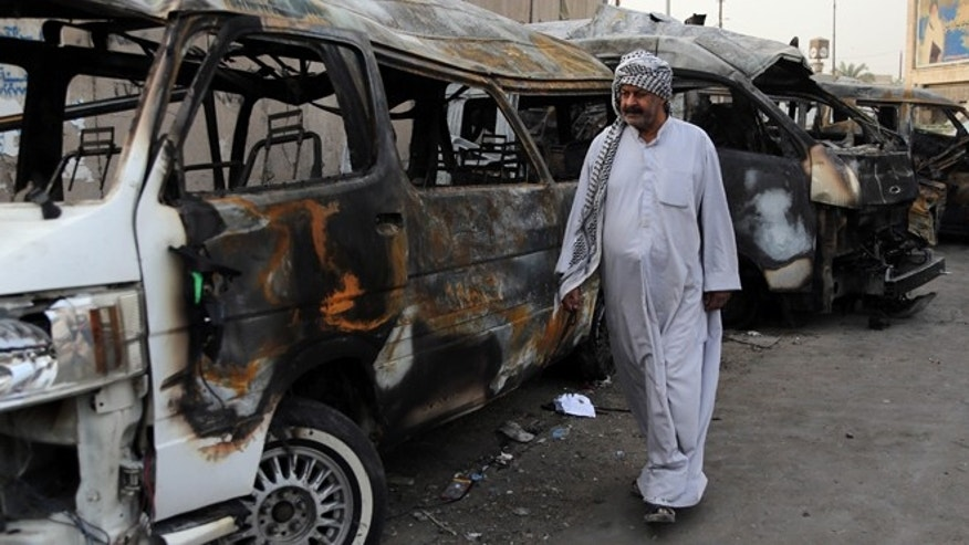Oct. 12, 2014: A man looks at the site of a car bomb attack in the Shula neighborhood of Baghdad, Iraq.
