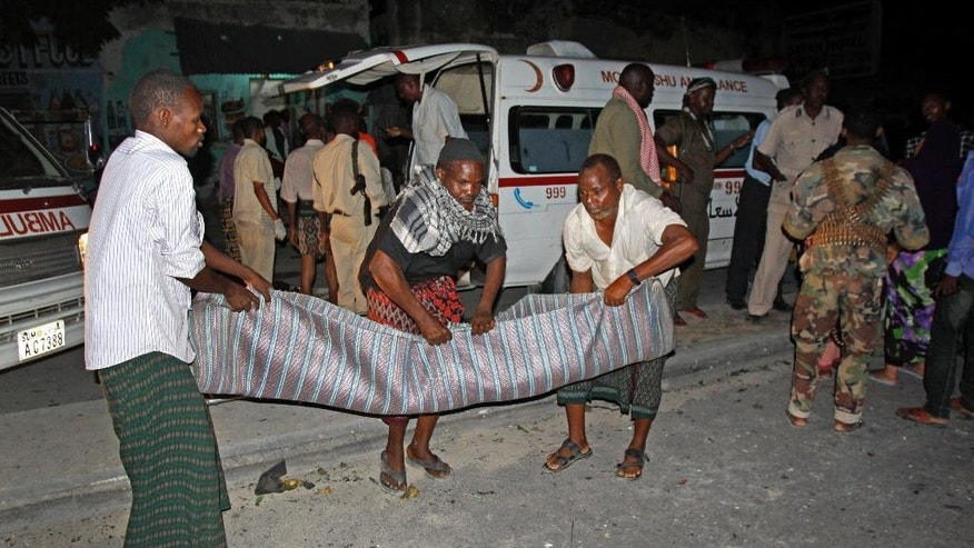 Somalis carry away a body from the scene of a car bomb attack in the capital Mogadishu, Somalia Sunday, Oct. 12, 2014. A car bomb exploded outside the popular Aroma cafe in Somalia's capital killing at least 11 people and wounding a number of others, a senior police official said Sunday, adding that the bomb was believed to have been detonated by remote control. (AP Photo/Farah Abdi Warsameh)
