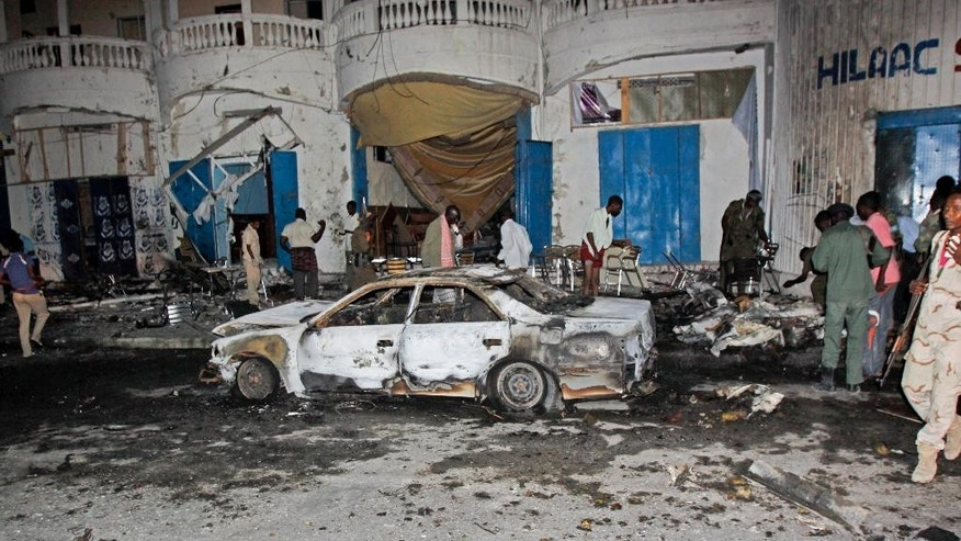 Somali security forces and others attend the scene of a car bomb attack in the capital Mogadishu, Somalia Sunday, Oct. 12, 2014. A car bomb exploded outside the popular Aroma cafe in Somalia's capital killing at least 11 people and wounding a number of others, a senior police official said Sunday, adding that the bomb was believed to have been detonated by remote control. (AP Photo/Farah Abdi Warsameh)
