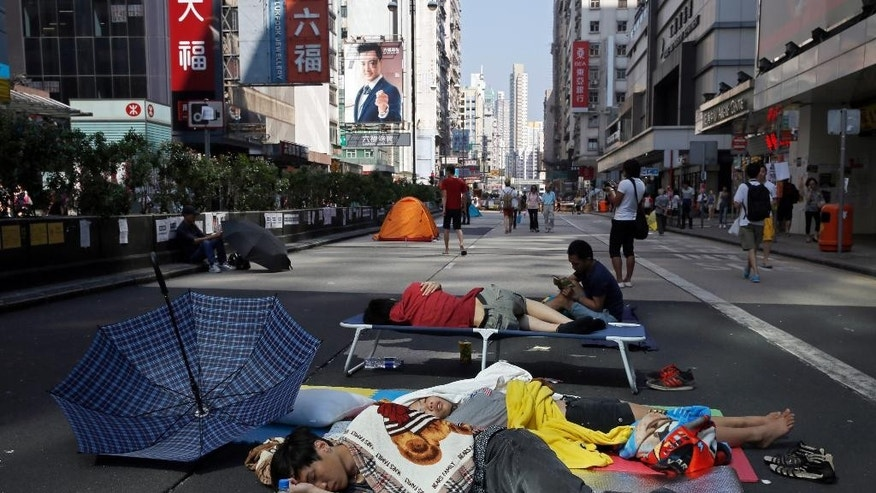 Pro-democracy protesters sleep in a main road in the occupied areas in Hong Kong's Mong Kok district Saturday, Oct. 11, 2014. Thousands of people are pouring into a main road in Hong Kong last night to show support for a pro-democracy protest after the government called off talks with student leaders. (AP Photo/Vincent Yu)
