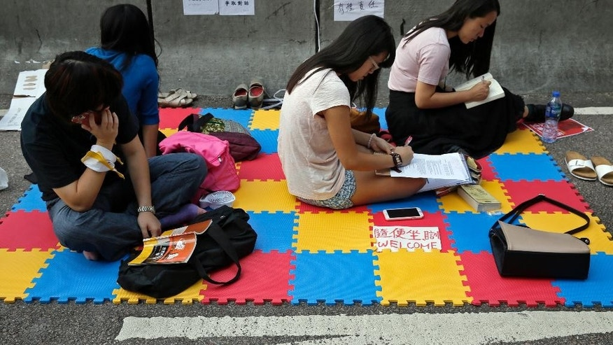 Pro-democracy students study at a main road in the occupied areas in Hong Kong's Admiralty district, Saturday, Oct. 11, 2014. Students and activists demanding a greater say in choosing the city's leader have vowed to stay until the government responds, while the government has repeatedly urged protesters to withdraw from the streets and allow the city to return to normal. (AP Photo/Vincent Yu)