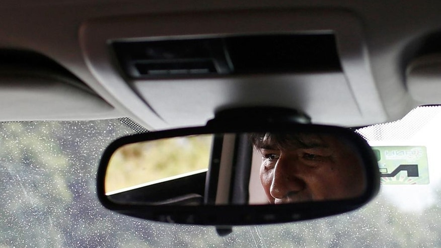 Bolivian President Evo Morales is reflected in his rearview mirror in Chapare, Bolivia, Saturday, Oct. 11, 2014, as he drives to the city where he'll vote in tomorrow's election. Morales seems certain to win an unprecedented third term in Sunday's presidential elections. (AP Photo/Juan Karita)