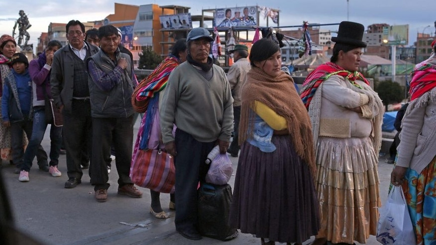 Residents line up as they wait for a bus in El Alto, Bolivia, Saturday, Oct. 11, 2014. Former coca growers' union leader Evo Morales seems certain to win an unprecedented third term in Sunday's presidential elections. (AP Photo/Martin Mejia)