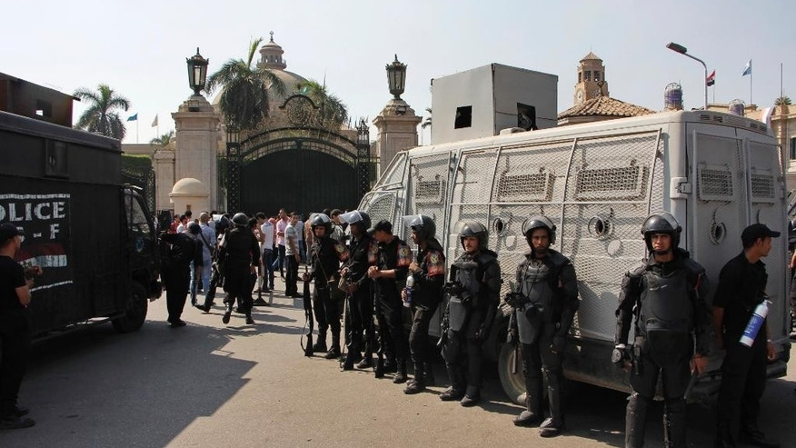 Egyptian security forces stand guard at Cairo University in Cairo, Egypt, Sunday, Oct. 12, 2014. Security officials said police backed by armored vehicles have stormed the campuses of at least two prominent Egyptian universities to quell anti-government protests by students. Sunday's largest rallies took place at Cairo and the Islamist al-Azhar universities. They were organized by supporters of ousted Islamist President Mohammed Morsi. (AP Photo/El Shorouk, Aly Hazzaa) EGYPT OUT