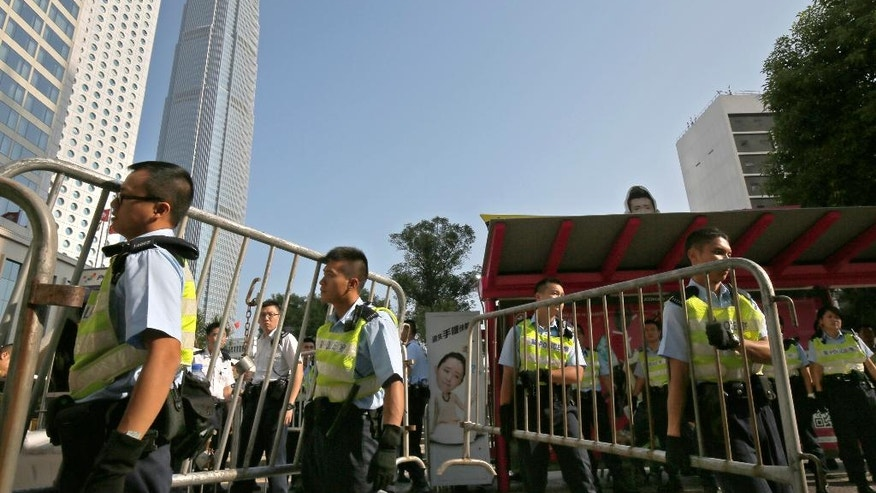 Police officers remove some barricades used by pro-democracy protesters who have been occupying main roads in the Asian financial center for two weeks in Hong Kong Monday, Oct. 13, 2014. Officers took away unmanned metal barricades at the edges of the city's Central financial district early Monday, ahead of the rush hour.  (AP Photo/Vincent Yu)