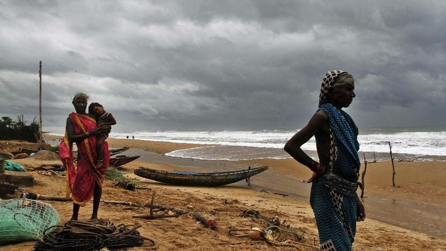 Oct. 11, 2014: Fisherwomen watch the sea waves before evacuating the place near Podampeta village, on the outskirts of Gopalpur beach in Ganjam district, 87 miles south of Bhubaneswar, India. (AP)