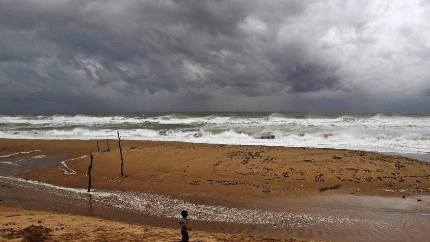 """An Indian boy plays on the beach as waves break on the Bay of Bengal coast near Gopalpur, in Ganjam district, 140 kilometers (87 miles) south of Bhubaneswar, India, Saturday, Oct. 11, 2014. The India Meteorological Department described Cyclone Hudhud as a """"very severe"""" storm that could pack winds of 195 kilometers (120 miles) per hour and cause torrential rains when it makes landfall near the port city of Visakhapatnam around noon Sunday. (AP Photo/Biswaranjan Rout)"""