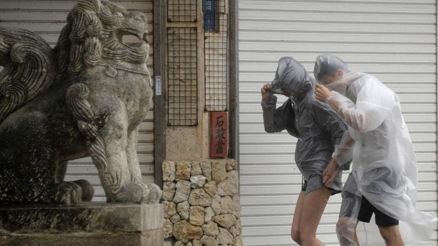 People wearing raincoat make their way through heavy wind and rain caused by typhoon Vongfong in Naha, Okinawa, Saturday, Oct. 11, 2014. The powerful typhoon poured heavy rains over Japan's southern island of Okinawa and was aiming at the next island of Kyushu on Sunday, becoming the second severe storm to hit in a week. (AP Photo/Kyodo News) JAPAN OUT, CREDIT MANDATORY