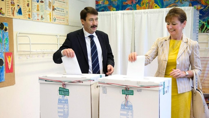 Hungarian President Janos Ader casts his vote with his wife Anita Herczegh during the municipal elections in Budapest, Hungary, Sunday, Oct. 12, 2014. (AP Photo/MTI, Szilard Koszticsak)