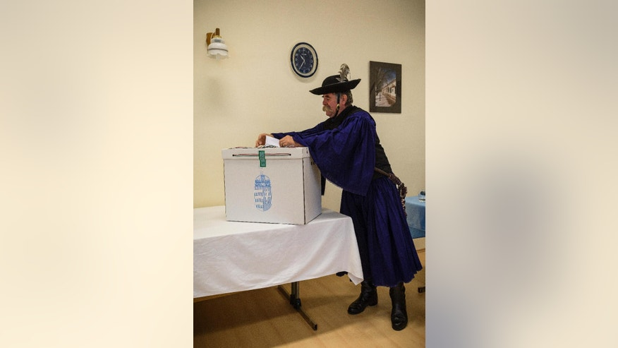 Sandor Szabo, a herdsman, casts his vote during municipal elections at a polling station in Hortobagy, 183 kms east of Budapest, Hungary, Sunday, Oct. 12, 2014. (AP Photo/MTI, Zsolt Czegledi)