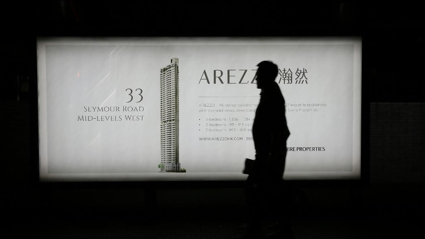 In this Saturday, Oct. 11, 2014 photo, a man walks past an advertisement for a high rise apartment building on a main road in Hong Kong's Central district, Wednesday, Oct. 8, 2014. In this city built on commerce, the political protests have churned up deeper questions, exposing a series of economic divides and deep unease over whether the territory's unique identity can survive in China's ever-growing shadow.  (AP Photo/Vincent Yu)