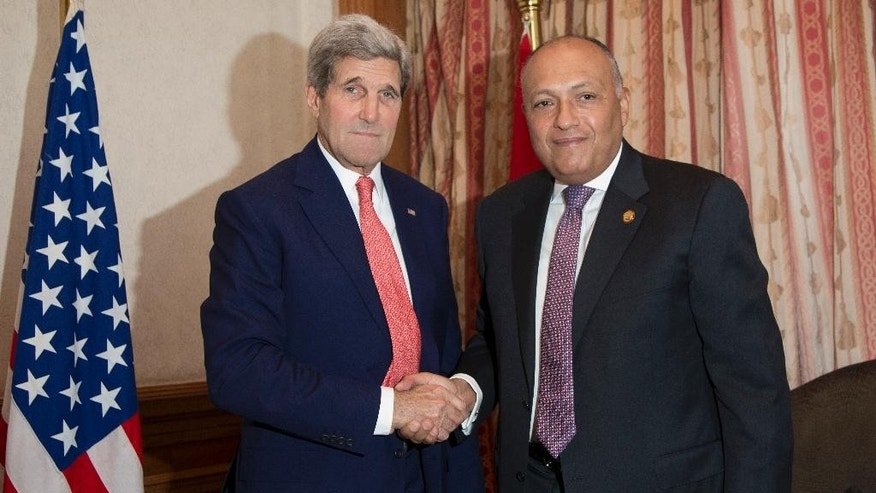 U.S. Secretary of State John Kerry shakes hands with Egypt Foreign Minister Sameh Shoukry in Cairo, Egypt, Sunday, Oct. 12, 2014, before a working breakfast during the Gaza Donor Conference. (AP Photo/Carolyn Kaster, Pool)
