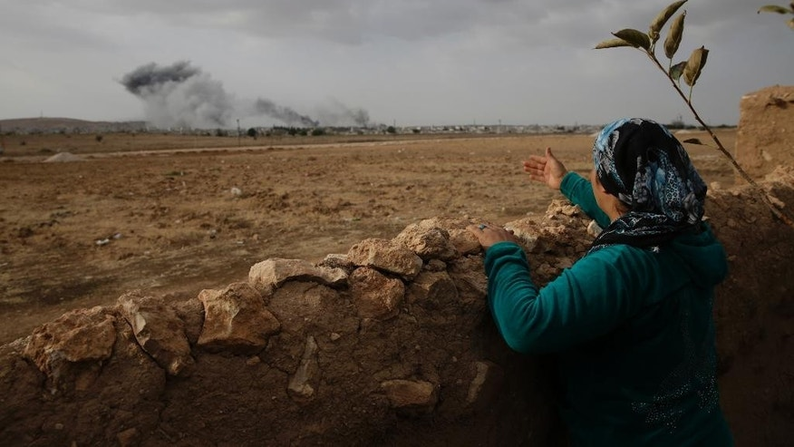 A Turkish Kurd, standing in Mursitpinar, in  the outskirts of Suruc, on the Turkey-Syria border, watches smoke from fires caused by strikes during fighting between militants of the Islamic State group and Kurdish forces in Kobani, Syria, background,  Sunday, Oct. 12, 2014. Kobani, also known as Ayn Arab, and its surrounding areas, has been under assault by extremists of the Islamic State group since mid-September and is being defended by Kurdish fighters. (AP Photo/Lefteris Pitarakis)