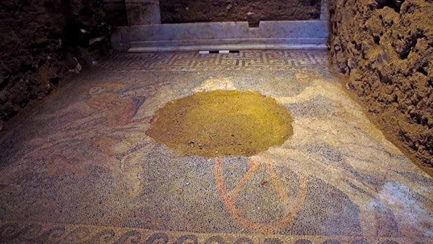 In this picture provided by Greece's Culture ministry on Sunday, Oct. 12, 2014, a partly damaged floor mosaic is shown inside an ancient Greek tomb, depicting a chariot driver, two horses and the Greek god Hermes. Archaeologists digging through an ancient grave at Amphipolis, northern Greece, uncovered the 3-by-4.5 meter (10-by-15 ft.) mosaic in what is likely the antechamber to the main burial room. (AP Photo/Greek Culture Ministry)