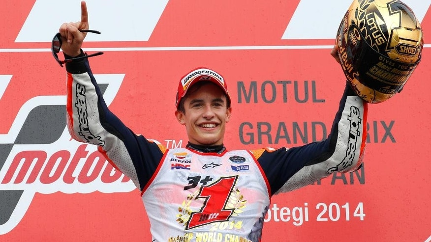 Spain's Marc Marquez celebrates during the awarding ceremony of Japanese Motorcycle Grand Prix at Twin Ring Motegi circuit in Motegi, north of Tokyo, Japan, Sunday, Oct. 12, 2014. Honda rider Marquez defended his MotoGP championship on Sunday when he finished second in the Grand Prix of Japan behind compatriot Jorge Lorenzo. (AP Photo/Shizuo Kambayashi)