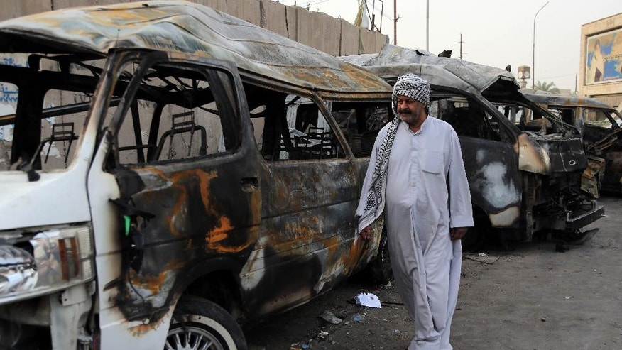 A man looks at the site of a car bomb attack in the Shula neighborhood of Baghdad, Iraq, Sunday, Oct. 12, 2014. A series of car bomb attacks in Iraq's capital killed and wounded dozens of people in Shiite areas Saturday, authorities said. (AP Photo/Karim Kadim)