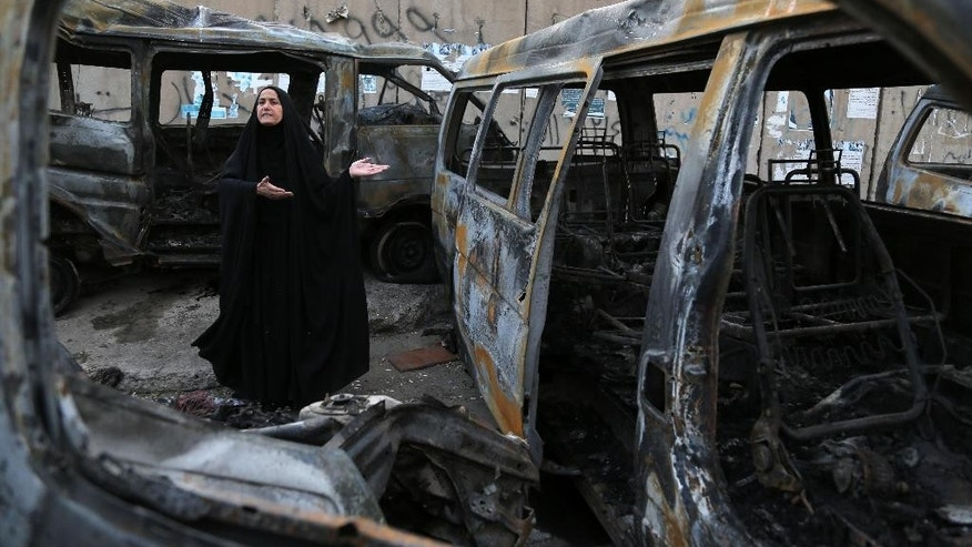 A woman reacts to the carnage at the site of a car bomb attack in the Shula neighborhood of Baghdad, Iraq, Sunday, Oct. 12, 2014. A series of car bomb attacks in Iraq's capital killed and wounded dozens of people in Shiite areas Saturday, authorities said. (AP Photo/Karim Kadim)