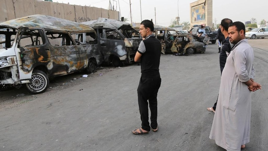 Civilians gather at the site of a car bomb attack in the Shula neighborhood of Baghdad, Iraq, Sunday, Oct. 12, 2014. A series of car bomb attacks in Iraq's capital killed and wounded dozens of people in Shiite areas Saturday, authorities said. (AP Photo/Karim Kadim)