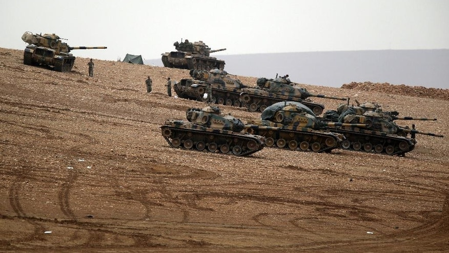 Turkish soldiers hold their positions with their tanks on a hilltop on the outskirts of Suruc, at the Turkey-Syria border, overlooking Kobani, Syria, during fighting between Syrian Kurds and the militants of Islamic State group, Sunday, Oct. 12, 2014. Kobani, also known as Ayn Arab, and its surrounding areas, has been under assault by extremists of the Islamic State group since mid-September and is being defended by Kurdish fighters.(AP Photo/Lefteris Pitarakis)