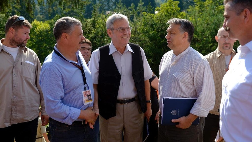 "In this picture taken Saturday, July 26, 2014, Mayor of Baile Tusnad Tibor Antal, second left, welcomes Hungarian Prime Minister Viktor Orban, second right, and Romanian MEP Laszlo Tokes, center, at the 25th Balvanyos Summer University and Students' Camp, where Orban delivered a speech in Baile Tusnad, Romania. In his speech, Orban said he wanted to turn Hungary into an ""illiberal state"" and that his efforts were being obstructed by civic groups who were ""paid political activists"" financed from abroad. As a young politician, Viktor Orban won plaudits for championing civil rights and free elections. Now as Hungary's prime minister, Western nations are alarmed at the way he is trying to consolidate power, including a government crackdown on rights groups. (AP Photo/MTI, Laszlo Beliczay)"