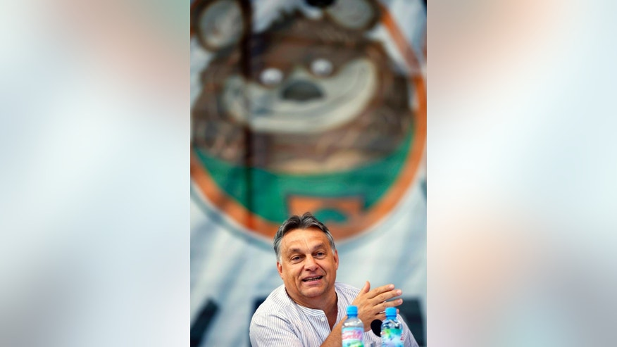 "In this picture taken Saturday, July 26, 2014, Hungarian Prime Minister Viktor Orban delivers his speech at the 25th Balvanyos Summer University and Students' Camp in Baile Tusnad, Romania. In his speech, Orban said he wanted to turn Hungary into an ""illiberal state"" and that his efforts were being obstructed by civic groups who were ""paid political activists"" financed from abroad. As a young politician, Viktor Orban won plaudits for championing civil rights and free elections. Now as Hungary's prime minister, Western nations are alarmed at the way he is trying to consolidate power, including a government crackdown on rights groups.  (AP Photo/MTI, Laszlo Beliczay)"