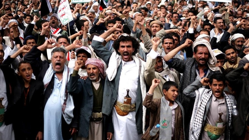 FILE - In this Thursday, Oct. 9, 2014 file photo, Houthi Shiite rebels chant slogans during a protest near the site of a suicide bombing in Sanaa, Yemen. Yemen's 2011 Arab Spring revolt began with a nucleus of young men and women, a mix of socialists, secularists and moderate Islamists seeking to end autocrat Ali Abdullah Saleh's 33-year rule and transform the poorest Arab nation into a democratic, modern society. In October 2014, nearly four years later, Yemen is in chaos and Shiite rebels have overrun the capital. Saleh is out of power, but remains powerful, with his loyalists infusing the political scene and the military. Attempts at real reform are in disarray. (AP Photo/Abdullrhman Huwais, File)