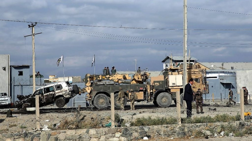 U.S. soldiers remove a destroyed vehicle from the site of a suicide attack in Kabul, Afghanistan, Monday, Oct. 13, 2014. An Afghan official says a suicide bomber targeting a NATO convoy in Kabul has killed one civilian and wounded three others. (AP Photo/Massoud Hossaini)