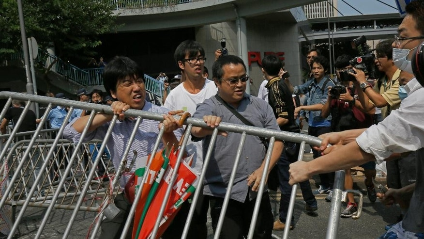 People remove the metal barricades that protesters have set up to block off main roads near the heart of the city's financial district, Hong Kong Monday, Oct. 13, 2014. An angry crowd tried to charge barricades used by pro-democracy protesters to occupy part of downtown Hong Kong as a standoff with authorities dragged into a third week. (AP Photo/Vincent Yu)