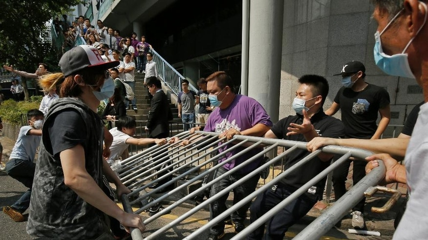 People wearing masks remove the metal barricades that protesters have set up to block off main roads near the heart of the city's financial district, Hong Kong Monday, Oct. 13, 2014. An angry crowd tried to charge barricades used by pro-democracy protesters to occupy part of downtown Hong Kong as a standoff with authorities dragged into a third week. (AP Photo/Vincent Yu)