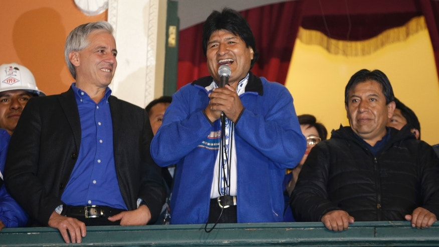 Bolivia's President Evo Morales speaks to supporters from the balcony of the presidential palace in La Paz, Bolivia, Sunday Oct. 12, 2014.  Evo Morales easily won an unprecedented third term as Bolivia's president Sunday according to an unofficial quick count of the vote. At left is Vice President Alvaro Garcia.(AP Photo/Martin Mejia)
