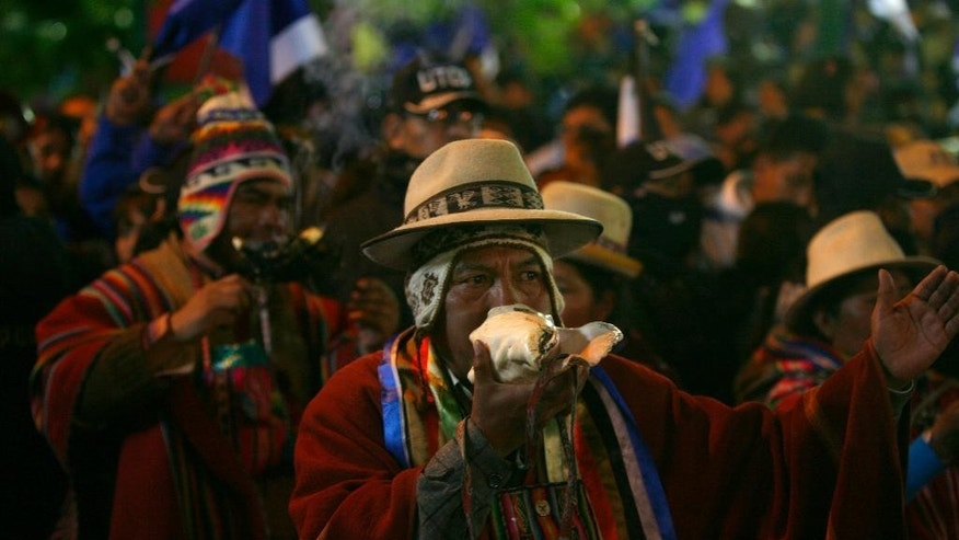 An Aymara indigenous blows a seashell in celebration as supporters wait for President Evo Morales outside the presidential palace in La Paz, Bolivia, Sunday Oct. 12, 2014.  Evo Morales easily won an unprecedented third term as Bolivia's president Sunday according to an unofficial quick count of the vote.(AP Photo/Enric Marti)