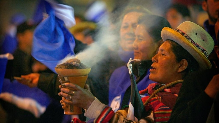 An Aymara indigenous woman burns incense in celebration as supporters wait for President Evo Morales outside the presidential palace in La Paz, Bolivia, Sunday Oct. 12, 2014.  Evo Morales easily won an unprecedented third term as Bolivia's president Sunday according to an unofficial quick count of the vote.(AP Photo/Enric Marti)