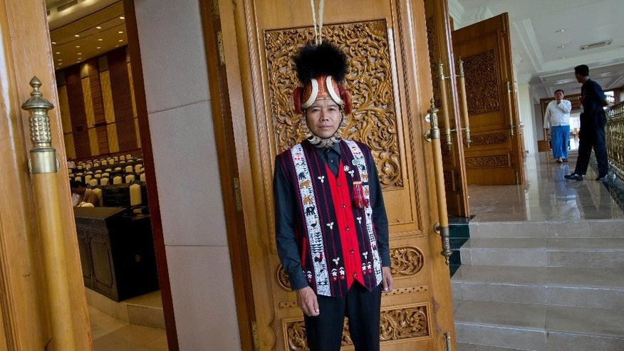 In this Sept. 17, 2014 photo, Myat Ko, an ethnic Naga member of Myanmar's Upper House, representing governing Union Solidarity and Development Party (USDP), poses for a photo outside the chambers wearing a traditional Naga hat in Naypyidaw, Myanmar. Myat Ko says his proudest achievement in Parliament is wearing his hat: a cane bowl adorned with wild boar tusks, hornbill feathers, a mountain goat's red mane and the fur and claws of a sun bear. It's about 2 feet tall, more than a century old, and attracts insects. (AP Photo/Gemunu Amarasinghe)