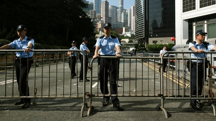 October 13, 2014: Police officers stand guard as they remove some of the barricades used by pro-democracy protesters who have been occupying main roads in the Asian financial center for two weeks in Hong Kong. Officers took away unmanned metal barricades at the edges of the city's Central financial district early Monday, ahead of the rush hour.  (AP Photo/Vincent Yu)
