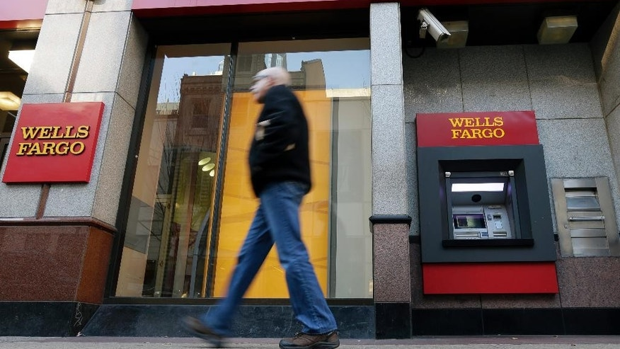 FILE - In this Wednesday, Dec. 19, 2012, file photo, a man walks past a Wells Fargo branch in Philadelphia. Wells Fargo and Chase, two of America's biggest retail banks, are quietly taking some callers' voiceprints to fight fraud, an Associated Press investigation has found. (AP Photo/Matt Rourke, File)
