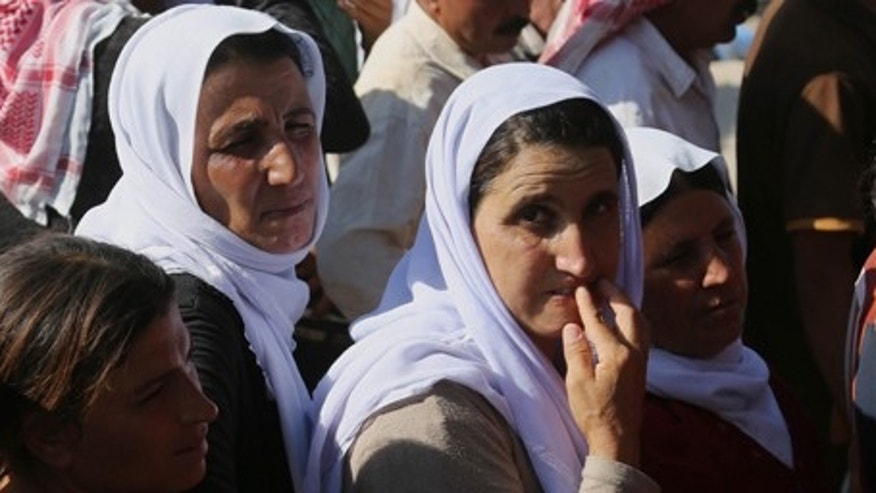 Aug. 12, 2014: Displaced Iraqis from the Yazidi community gather for humanitarian aid at Nowruz camp, in Derike, Syria.