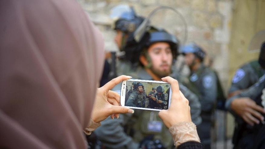 A Palestinian woman takes photos of Israeli border police during clashes in the Old City of Jerusalem, Monday Oct. 13, 2014.  Israeli police clashed with young Palestinian protesters on Monday demonstrating against Jews visiting the Al-Aqsa Mosque compound, Islam's third holiest site, a spokeswoman said. (AP Photo/Mahmoud Illean)