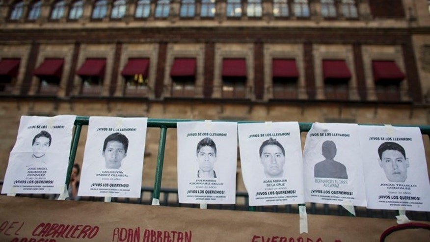 "Flyers printed with the faces of some of the 43 missing students and reading ""You took them alive. We want them back alive,"" hang on a fence in front of the National Palace, as thousands marched to demand the government find the students who disappeared in southern Guerrero State, in Mexico City, Wednesday, Oct. 8, 2014. Investigators still had no word on whether the 28 bodies found in a mass grave over the weekend included any of the missing students, who disappeared after two attacks allegedly involving Iguala police in which six people were killed and at least 25 wounded. (AP Photo/Rebecca Blackwell)"