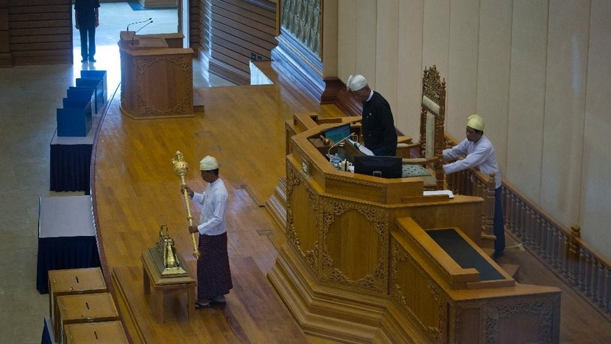 "In this Sept. 17, 2014 photo, a chairperson and Parliamentary staff with turban known as a ""gaun baun"" begin a sitting while security guard standing guard in the background at Myanmar's Upper House in Naypyidaw, Myanmar. The dress code in Parliament's chambers, based on the sumptuary laws of the king's courts in Mandalay, reflects the major political camps, and the legislature's ethnic makeup. (AP Photo/Gemunu Amarasinghe)"