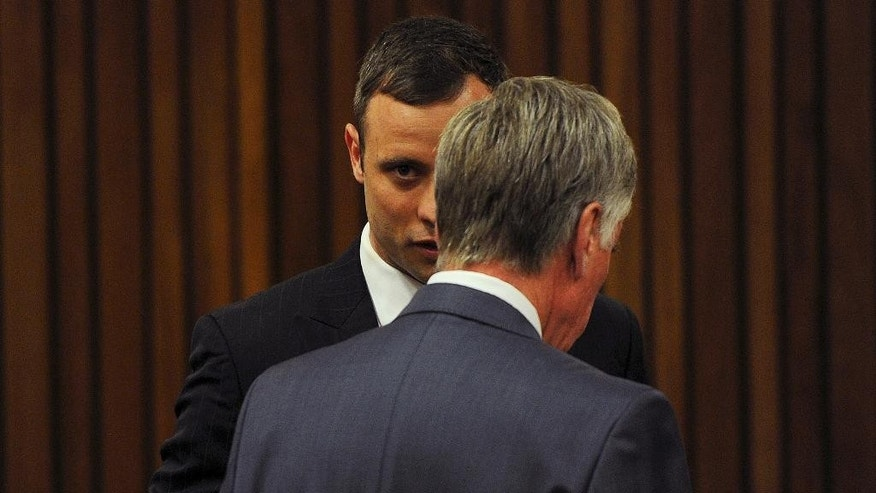 Oscar Pistorius, left, talks with one of his defense lawyers in court Monday, Oct. 13, 2014 to face sentencing for the shooting death of his girlfriend Reeva Steenkamp. Pistorius was found guilty last month on a culpable homicide charge. The defense have started arguing in mitigation of sentence. (AP Photo/Werner Beukes. Pool)