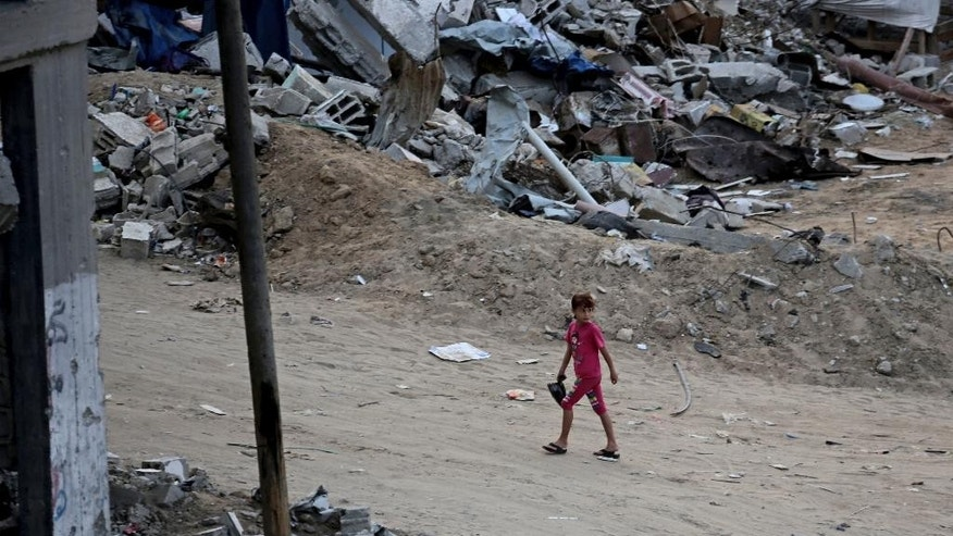 A Palestinian girl walks between the rubble of destroyed buildings in Shijaiyah neighborhood of Gaza City in the northern Gaza Strip, Sunday, Oct. 12, 2014. Delegates representing some 50 nations and 20 regional and international organizations attended a donor conference in Cairo, Egypt, on Sunday to help Gaza rebuild after the war between Israel and Gaza's militant Islamic group Hamas this summer. Organizers of the Cairo conference hope pledges of over 5 billion dollars will be paid over the period of three years to aid reconstruction in the Gaza Strip, which borders Israel and Egypt. Both countries have blockaded Gaza since Hamas took power there in 2007, causing the territory of 1.8 million people economic hardships and high unemployment. (AP Photo/Adel Hana)