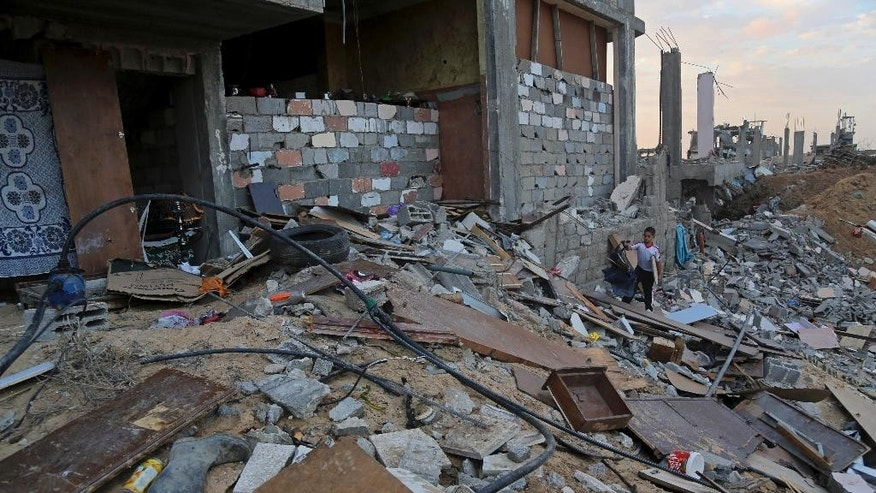 A Palestinian collects wood from the rubble of his destroyed home in Shijaiyah neighborhood of Gaza City in the northern Gaza Strip, Sunday, Oct. 12, 2014. Delegates representing some 50 nations and 20 regional and international organizations attended a donor conference in Cairo, Egypt, on Sunday to help Gaza rebuild after the war between Israel and Gaza's militant Islamic group Hamas this summer. Organizers of the Cairo conference hope pledges of over 5 billion dollars will be paid over the period of three years to aid reconstruction in the Gaza Strip, which borders Israel and Egypt. Both countries have blockaded Gaza since Hamas took power there in 2007, causing the territory of 1.8 million people economic hardships and high unemployment. (AP Photo/Adel Hana)