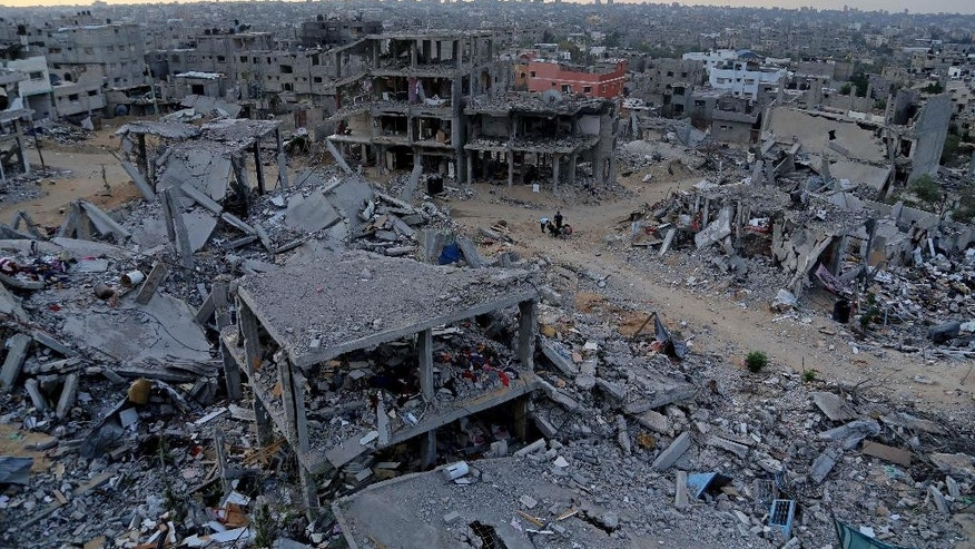 Palestinians sit between the rubble of their destroyed building in Shijaiyah, neighborhood of Gaza City, in the northern Gaza Strip, Sunday, Oct. 12, 2014. Delegates representing some 50 nations and 20 regional and international organizations attended a donor conference in Cairo, Egypt, on Sunday to help Gaza rebuild after the war between Israel and Gaza's militant Islamic group Hamas this summer. Organizers of the Cairo conference hope pledges of over 5 billion dollars will be paid over the period of three years to aid reconstruction in the Gaza Strip, which borders Israel and Egypt. Both countries have blockaded Gaza since Hamas took power there in 2007, causing the territory of 1.8 million people economic hardships and high unemployment. (AP Photo/Adel Hana)