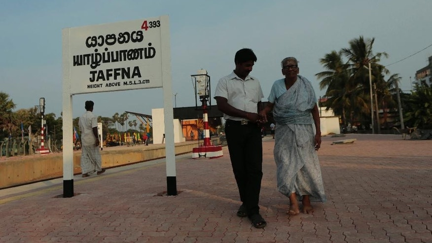 "An elderly Sri Lankan ethnic Tamil woman is helped by a man as they walk along a platform at the Jaffna railway station in Sri Lanka, Sunday, Oct. 12, 2014. The ""Queen of Jaffna,"" a once-popular train linking the ethnic Tamil's northern heartland to the rest of Sri Lanka before a bloody civil war cut the link 24 years ago, chugs back into service this coming week, reinforcing the government's authority in a region once controlled by Tamil rebels.(AP Photo/Eranga Jayawardena)"