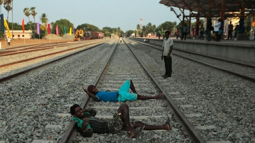 "Sri Lankan ethnic Tamil workers react to the camera as they rest on a rail track at the Jaffna railway station Sri Lanka, Sunday, Oct. 12, 2014. The ""Queen of Jaffna,"" a once-popular train linking the ethnic Tamil's northern heartland to the rest of Sri Lanka before a bloody civil war cut the link 24 years ago, chugs back into service this coming week, reinforcing the government's authority in a region once controlled by Tamil rebels.(AP Photo/Eranga Jayawardena)"