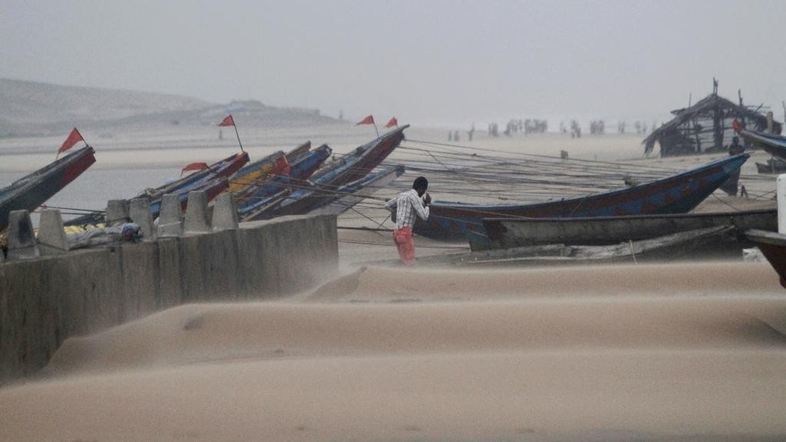 An Indian fisherman walks near the anchored fishing boats as strong winds blow a day after a powerful cyclone pounded the Bay of Bengal coast in Gopalpur, Orissa, about 285 kilometers (178 miles) north east of Visakhapatnam, India, Monday, Oct. 13, 2014. Cyclone Hudhud that slammed into India's eastern seaboard weakened as it moved inland Monday. (AP Photo/Biswaranjan Rout)
