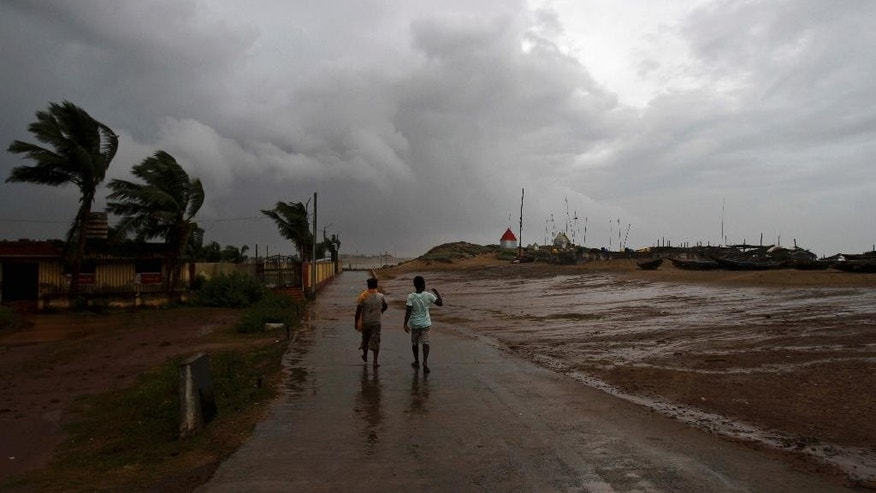 Two Indian villagers walk through the Bay of Bengal coast at Gopalpur, Orissa, about 285 kilometers (178 miles) north east of Visakhapatnam, India, Sunday, Oct. 12, 2014. A powerful cyclone was pounding a large swath of India's eastern seaboard with heavy rain and strong winds on Sunday, killing at least two people and causing major damage to buildings and crops, in one of two storms lashing Asia. (AP Photo/Biswaranjan Rout)